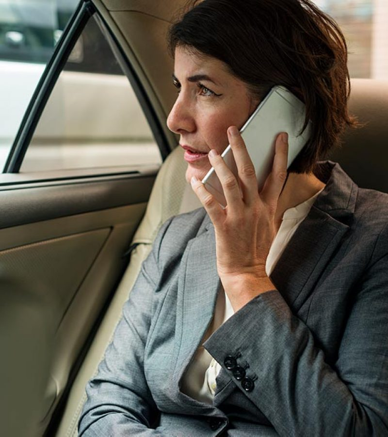 businesswoman-talking-using-phone-car-inside-PATXU3G